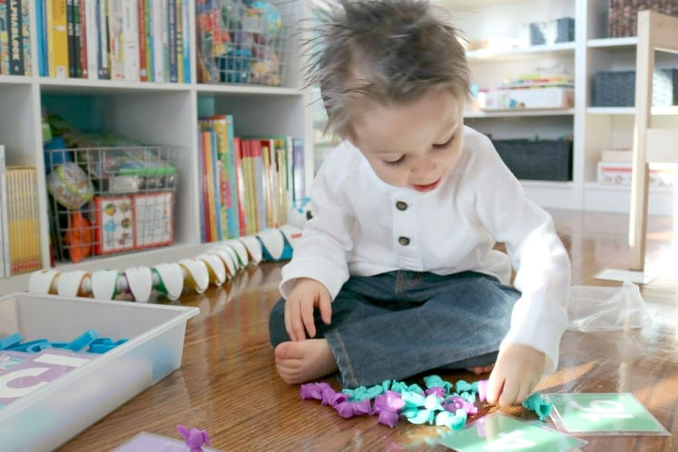 toddler sitting on floor counting manipulatives