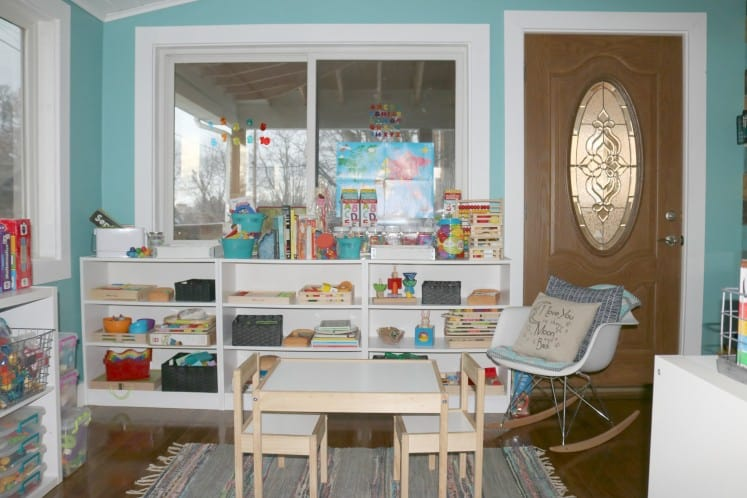 child's play area with table and chairs, rocking chair, and bookshelves filled with toys