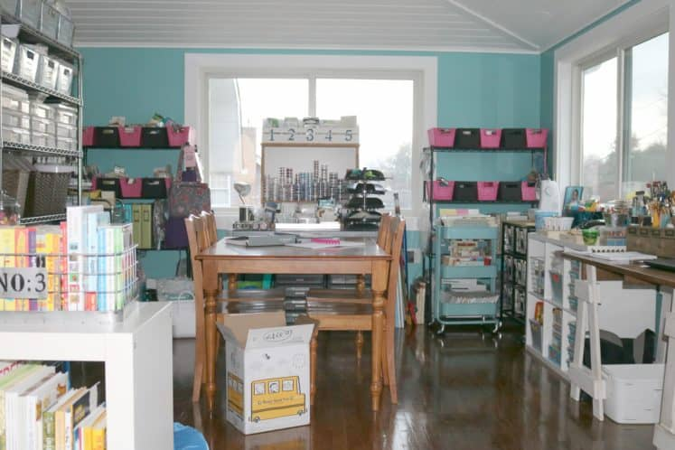 wooden table and chairs in center of craft room