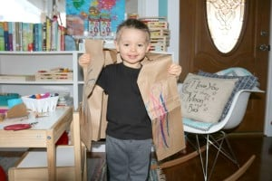 preschooler wearing colorful coat bible story craft made from brown paper bag and paint sticks