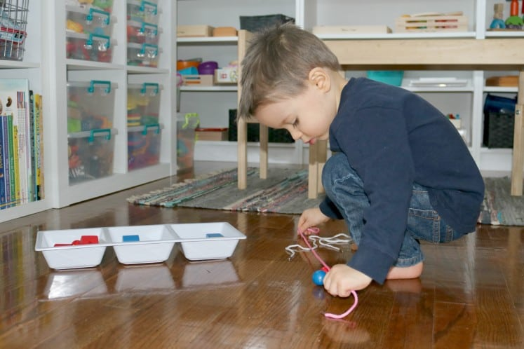 preschooler holding a piece of string against the floor