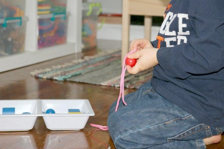 preschooler sitting on the floor stringing beads