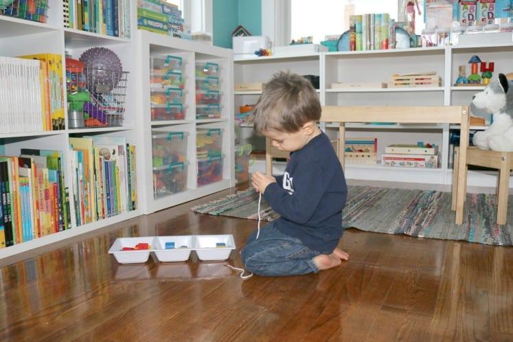 preschooler sitting on floor focused on stringing beads