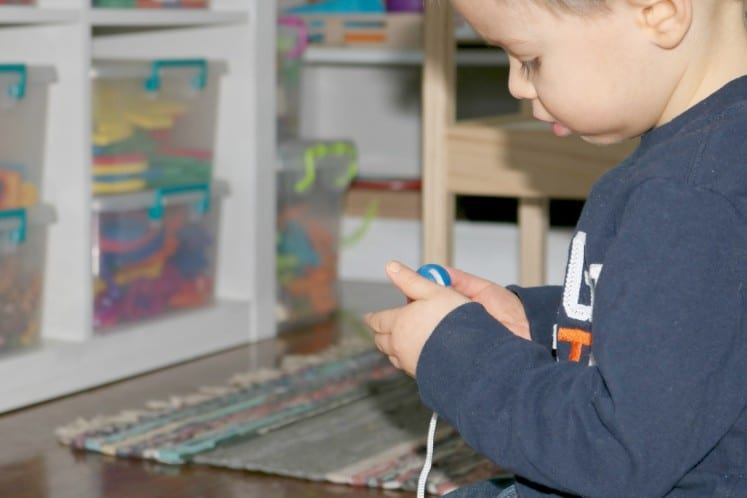 preschooler pulling bead on to string