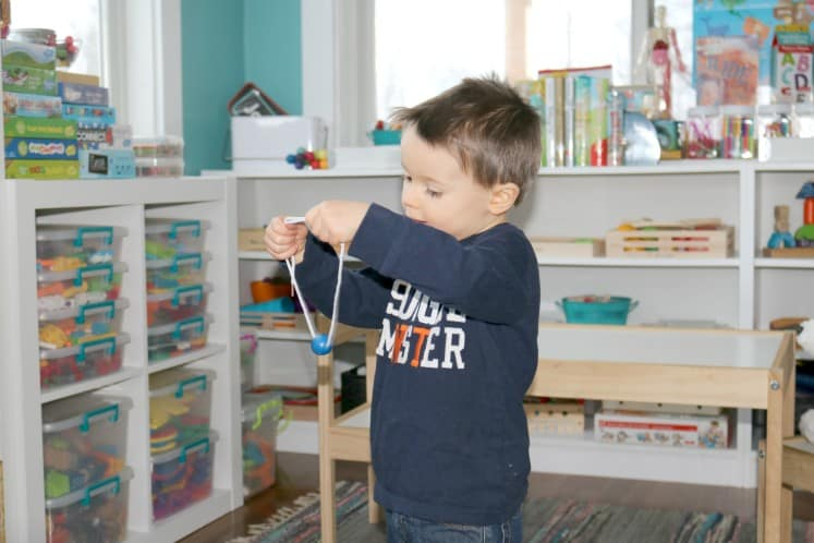 preschooler holding up bead on string