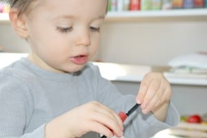 preschooler stringing cut straw on to pipe cleaner