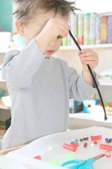 preschooler putting bead on to black pipe cleaner