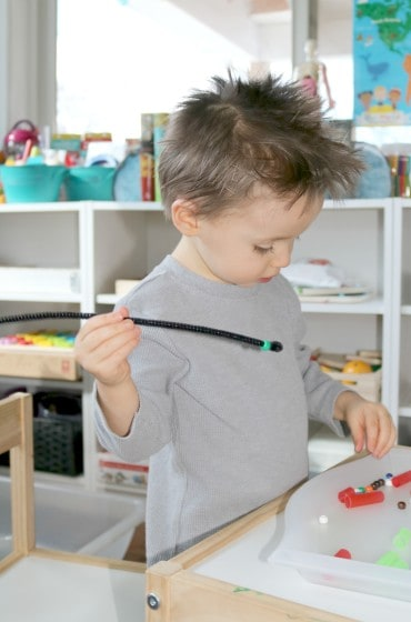 preschooler picking up bead from tray to string on to pipe cleaner