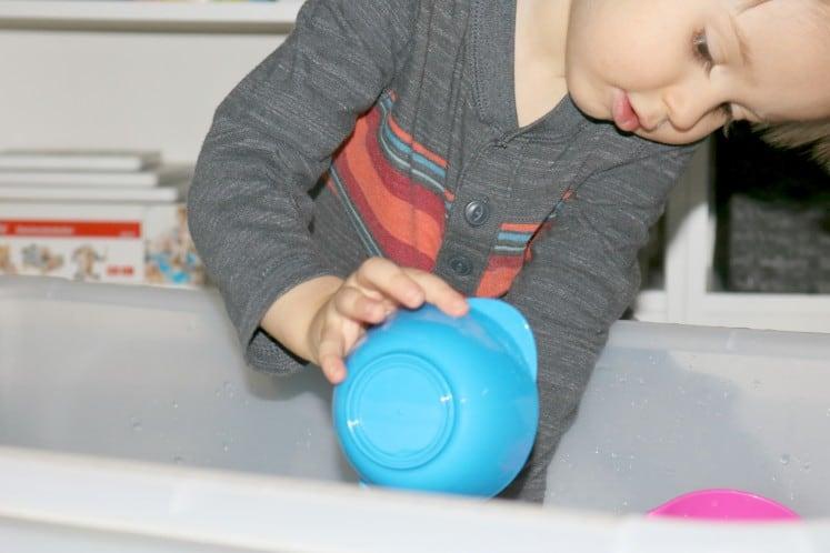 preschooler dumping water from cup into sensory bin