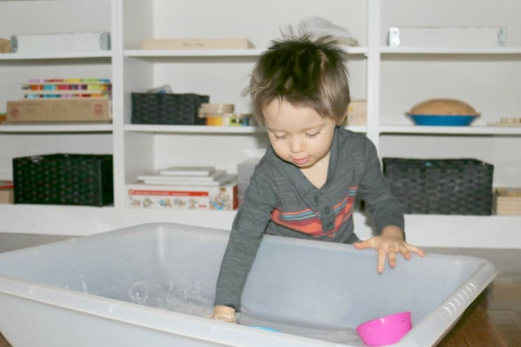 preschooler splashing around in sensory bin filled with water