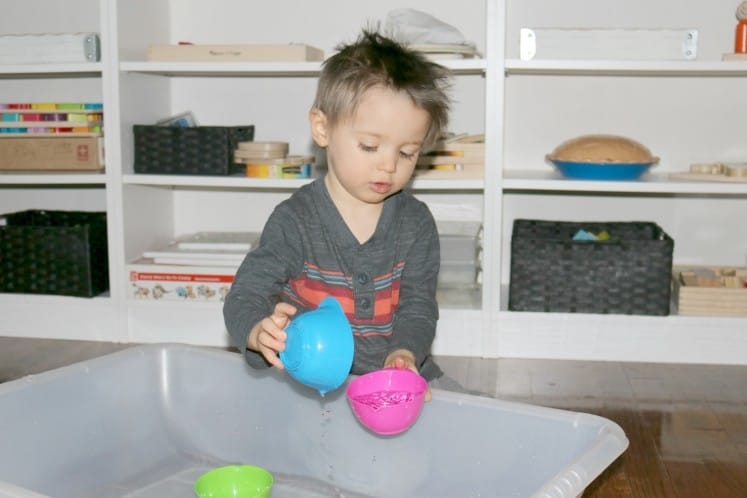 preschooler pouring water from one cup to another