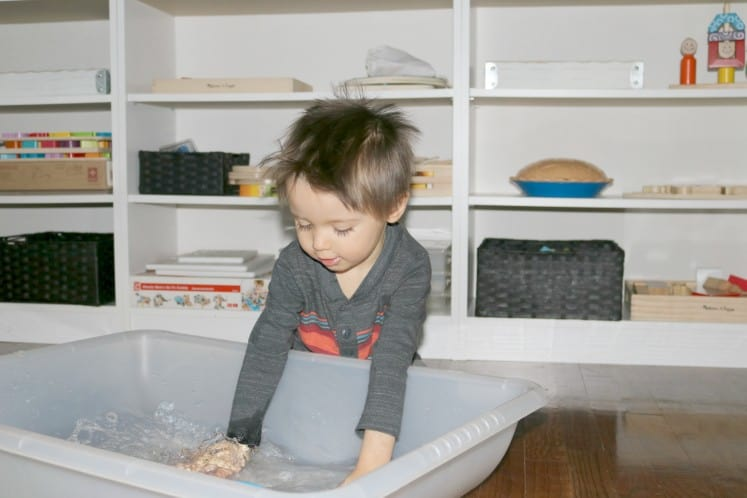 preschooler using hands to make waves in sensory bin filled with water