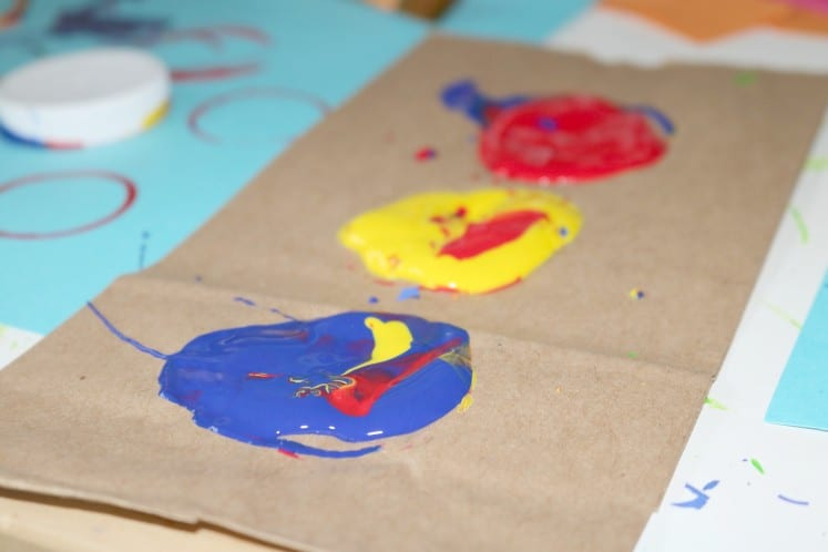 brown paper bag with globs of paint in primary colors