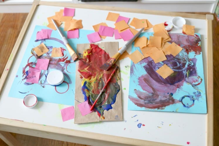 preschoolers' process art and painting supplies scattered on table