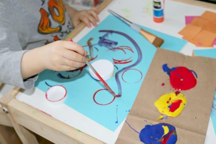 preschooler painting on blue cardstock