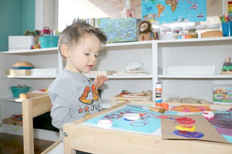 preschooler looking at his process art