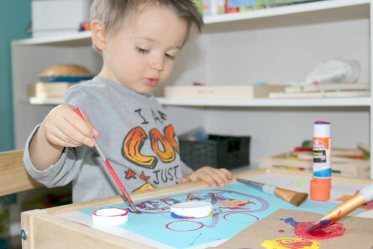 preschooler painting with primary colors on blue cardstock