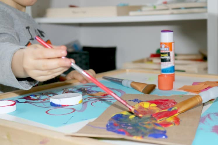 preschooler dipping brush in paint