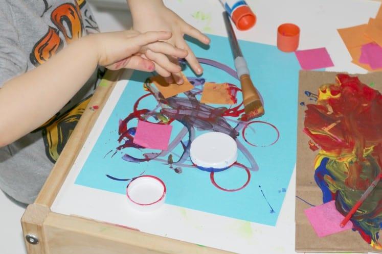 preschooler gluing tissue paper square on cardstock