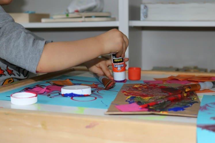 preschooler adding glue to blue cardstock