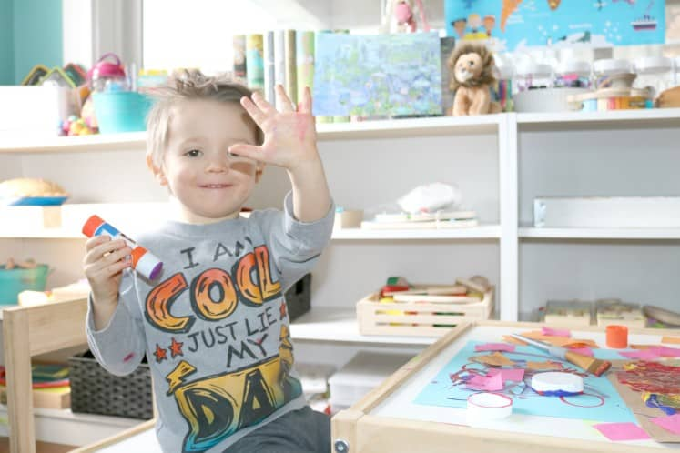 preschooler holding up hand covered in paint