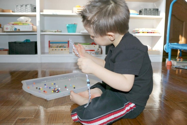 preschooler stringing beads on silver pipe cleaner to make wire sculpture