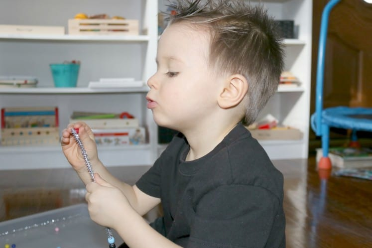 preschooler putting bead on silver pipe cleaner to make wire sculpture