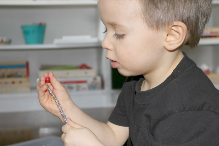 toddler putting red bead on silver pipe cleaner