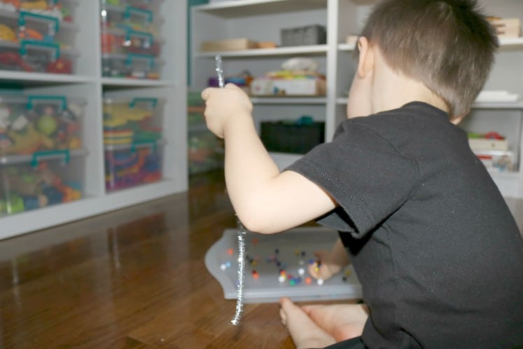 preschooler grabbing bead from tray to string on silver pipe cleaner