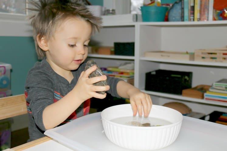 preschooler putting rock in to bowl of water