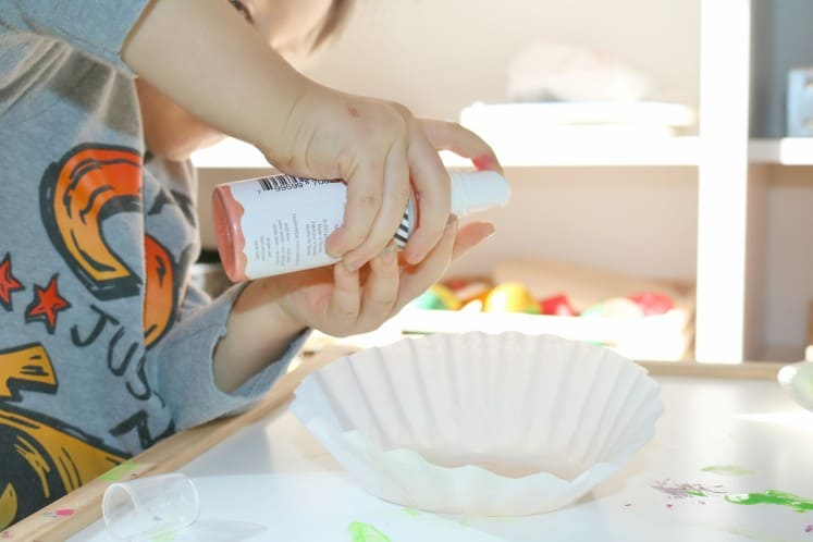 preschooler using spray ink to make water lilies from coffee filters