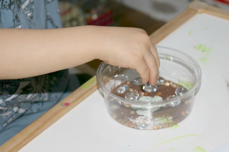 preschooler adding gems to pond process art in clear container