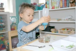 preschooler adding water to pond process art