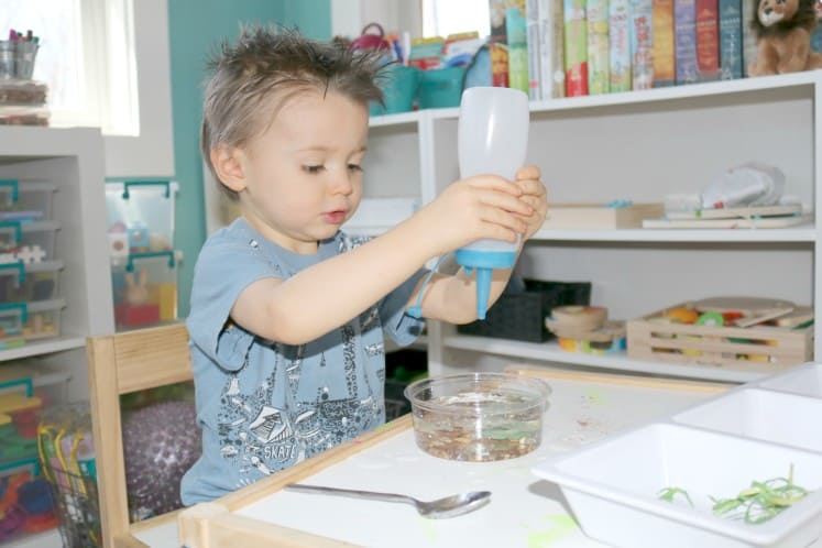preschooler adding water to pond process art