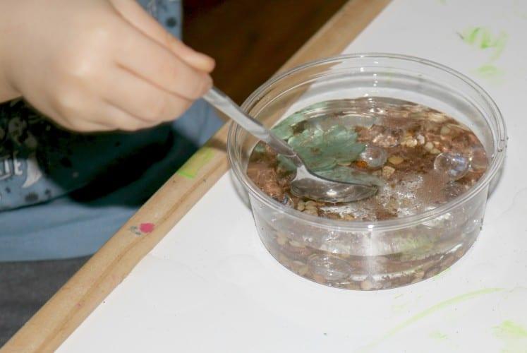 preschooler stirring water with spoon