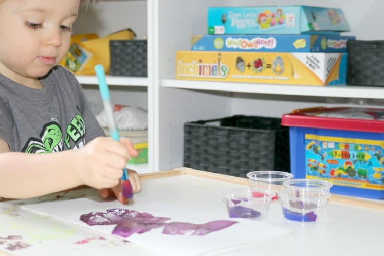 preschooler making butterfly wings with paint