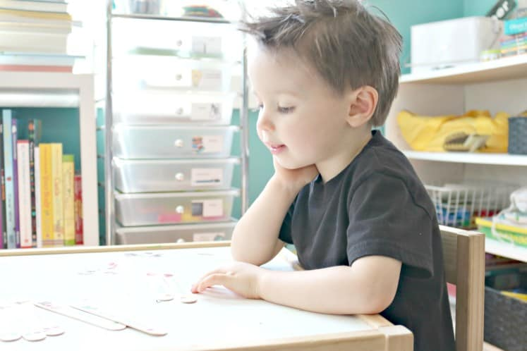 preschooler putting together craft stick puzzle