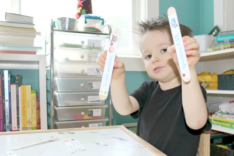 preschooler holding up craft stick puzzle pieces