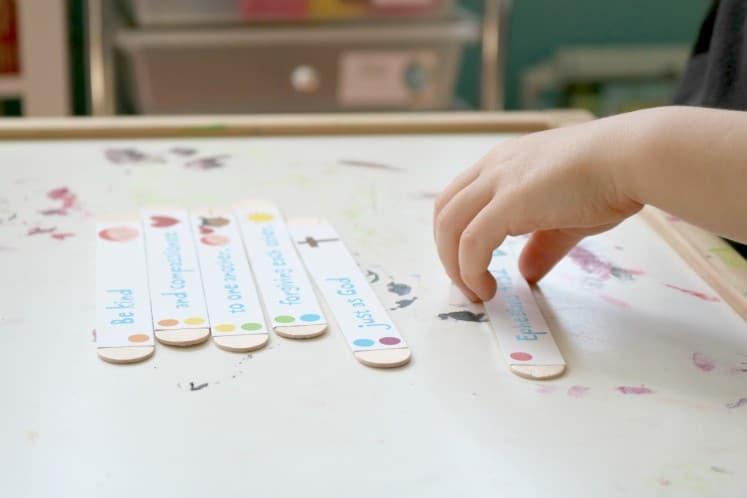 preschooler putting together craft stick bible verse puzzle