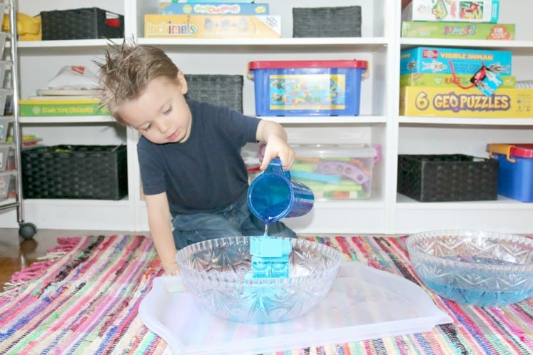 preschooler pouring water over blocks in bowl