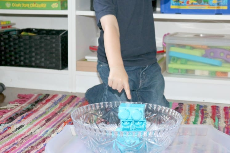 preschooler pointing at blocks in bowl filled with water
