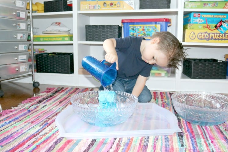 preschooler dumping pitcher of water over blocks in bowl
