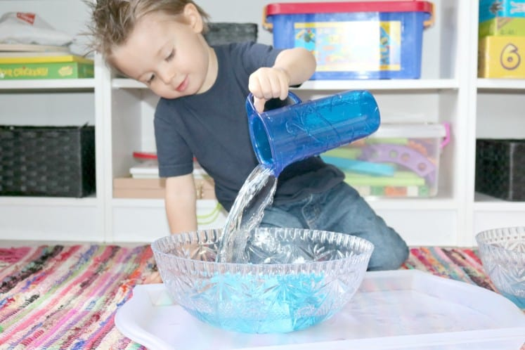 preschooler using water to knock over blocks in bowl