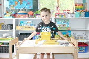 preschooler standing behind reading curriculum stacked on table