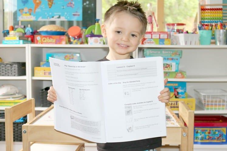 preschooler holding up Teacher's Manual