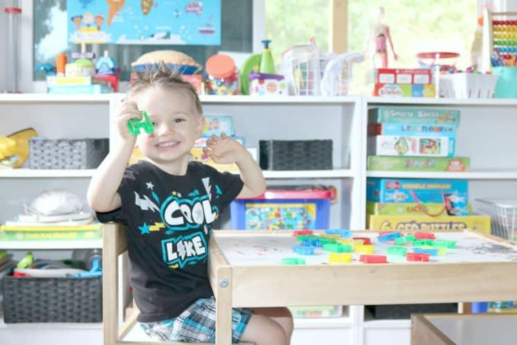 preschooler holding up letter cookie cutter
