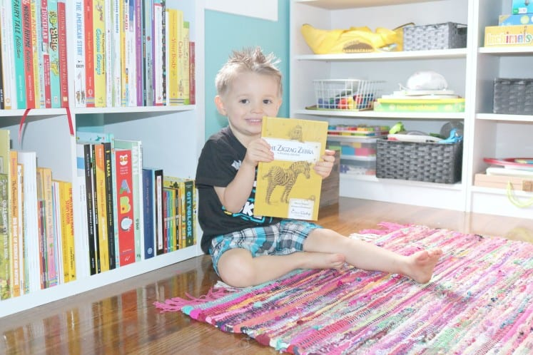 preschool sitting on the floor holding a reader