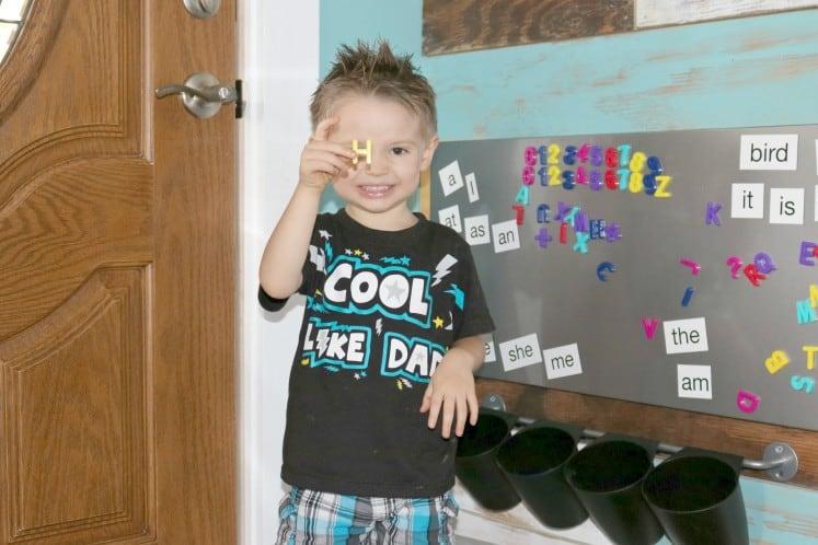 preschooler holding up magnetic letter