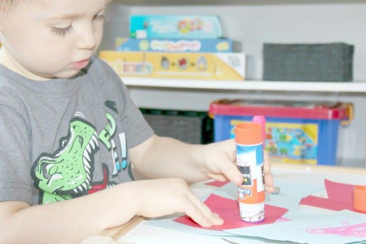 preschooler putting glue on cardstock