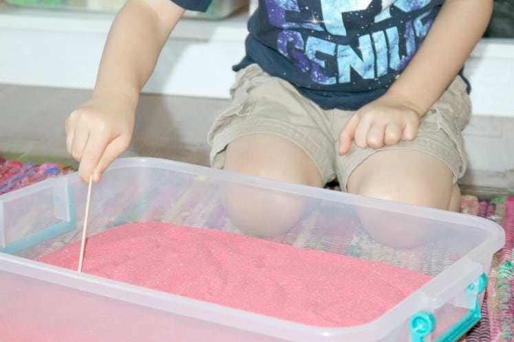 preschool stirring sand with craft stick